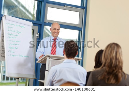 Happy businessman giving presentation to coworkers while standing at podium in office - stock photo