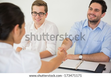 Happy businessman greeting female colleague in office meeting