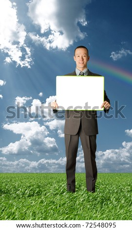 happy businessman holding blank white card in his hands outdoors