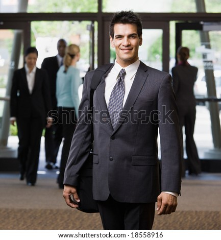 Happy businessman holding briefcase in office lobby - stock photo