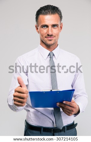 Happy businessman holding clipboard and showing thumb up isolated on a white background. Looking at camera - stock photo