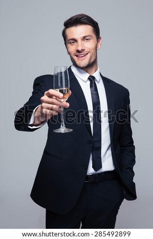 Happy businessman holding glass of champagne over gray background and looking at camera - stock photo