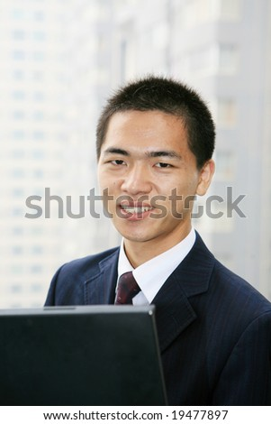 Happy businessman holding laptop computer