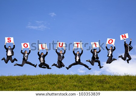 happy businessman holding solution text and jumping on the green field