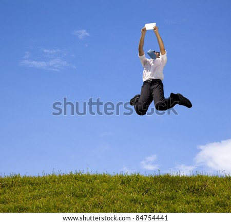 happy businessman holding touch pad and jumping on the hill