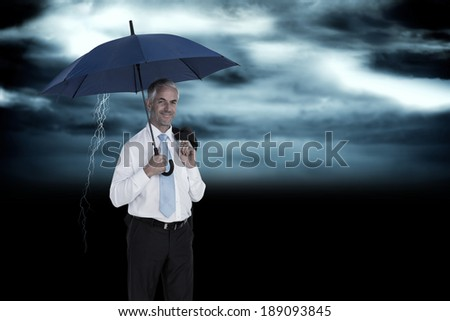 Happy businessman holding umbrella against stormy dark sky with lightning bolt