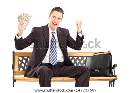 Happy businessman in black suit sitting on a wooden bench and holding US dollars isolated on white background - stock photo