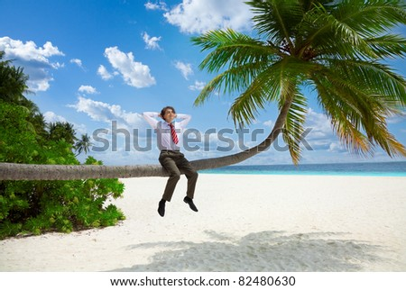 Happy businessman in formal clothes and tie sitting on the palm and relax - stock photo