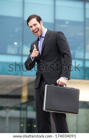 happy businessman in front of an office building  - stock photo