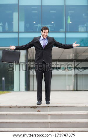 happy businessman in front of an office building with hands open on stairs - stock photo