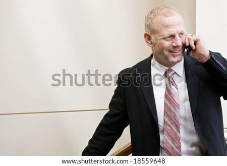 Happy businessman in full suit and tie talking on cell phone - stock photo