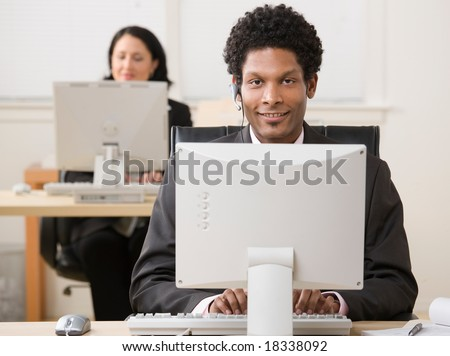 Happy businessman in headset working on computer with co-worker in background - stock photo