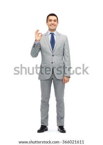 happy businessman in suit showing ok hand sign - stock photo