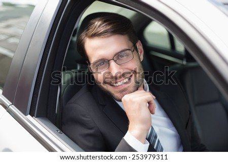 Happy businessman in the drivers seat in his car - stock photo