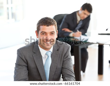 Happy businessman in the foreground during a meeting with a colleague at the office - stock photo