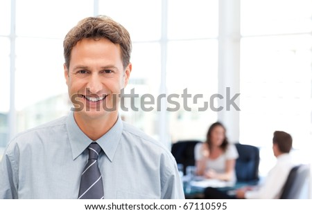 Happy businessman in the foreground while his team is working at a table - stock photo