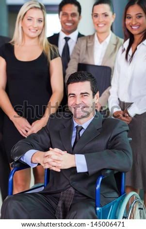happy businessman in wheelchair with colleagues - stock photo
