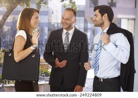 Happy businessman introducing new partner to attractive female colleague, outdoors. Suit and tie. - stock photo