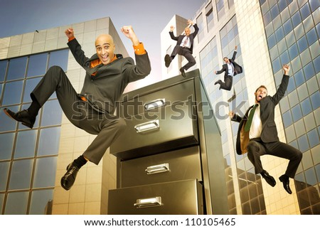 happy businessman jumping from binder in a business center - stock photo
