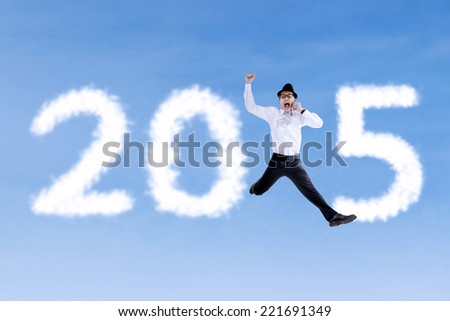 Happy businessman jumping on the sky while calling and forming number 2015 - stock photo