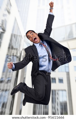 Happy businessman jumping outdoors - stock photo