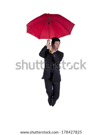 Happy businessman jumping protected by a red umbrella (some motion blur) - stock photo