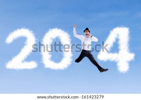 Happy businessman jumping with clouds of 2014 and using a telephone - stock photo