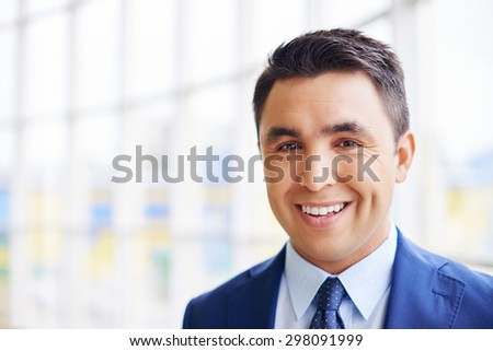Happy businessman looking at camera with smile - stock photo