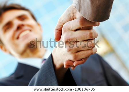 Happy businessman making handshake with businesswoman at meeting - stock photo