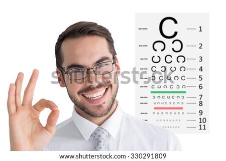 Happy businessman making okay gesture against eye test - stock photo