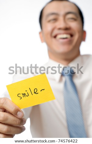 Happy businessman of Asian holding yellow card written smile words, closeup portrait. - stock photo