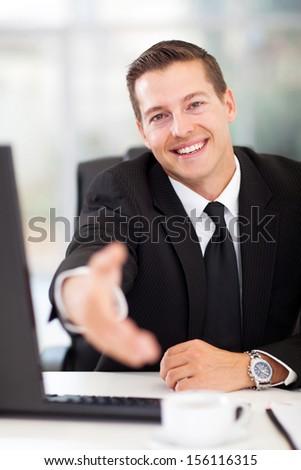 happy businessman offering handshake in office - stock photo