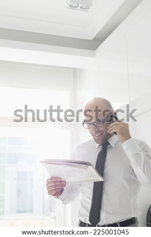 Happy businessman on call while reading newspaper at home