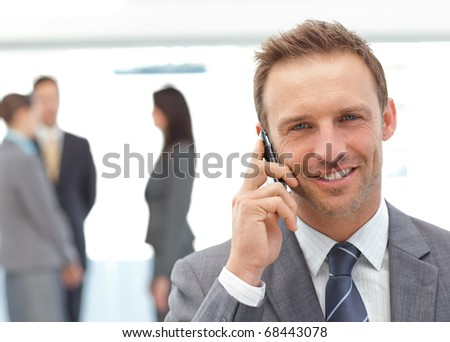 Happy businessman on the phone while his team working on the background - stock photo