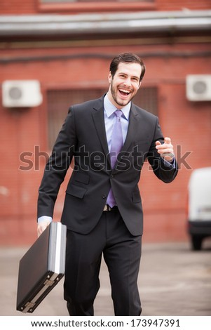 happy businessman on the street with his briefcase in his hand - stock photo