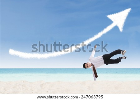 Happy businessman perform success move at beach under up arrow sign - stock photo