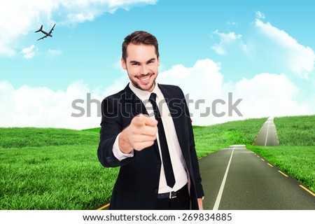 Happy businessman pointing at camera against road leading out to the horizon - stock photo