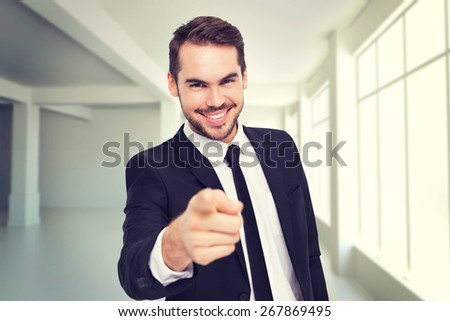 Happy businessman pointing at camera against white room with windows - stock photo