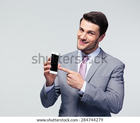 Happy businessman pointing finger on blank smartphone screen over gray background - stock photo