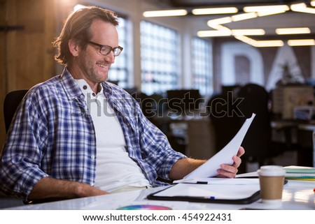 Happy businessman reading documents while sitting at desk in creative office