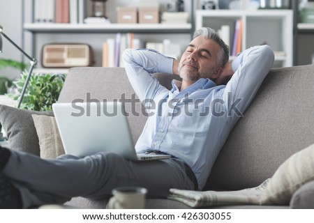 Happy businessman relaxing at home on the couch with a laptop on his lap, he is sleeping with hands behind head - stock photo