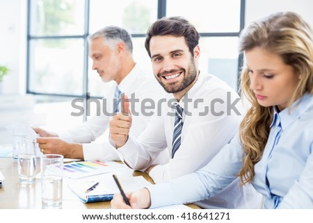 Happy businessman showing thumbs up in a meeting at office