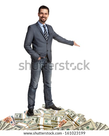 Happy businessman shows the way how to make a lot of money / hospitable person standing on a pile of banknotes - isolated on white background  - stock photo