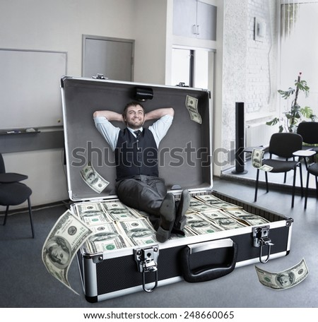 Happy businessman sits in the case full of dollars - stock photo