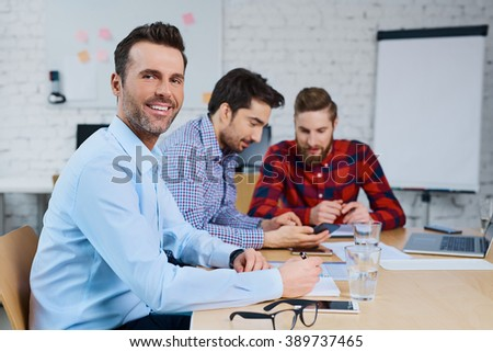 Happy businessman sitting at desk with business partners, coworkers