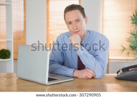 Happy businessman sitting at his desk in his office - stock photo