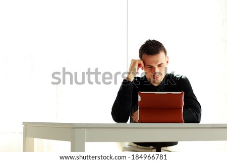 Happy businessman sitting at the table with tablet computer isolated on a white background
