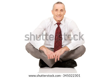 Happy businessman sitting cross-legged on the floor.