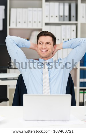 Happy businessman sitting daydreaming at the office relaxing with his hands clasped behind his head looking up into the air with a smile - stock photo