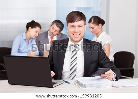 Happy Businessman Sitting In Front Of His Colleagues Working At Desk